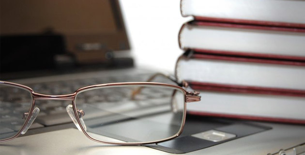 Photo of eyeglasses books laptop